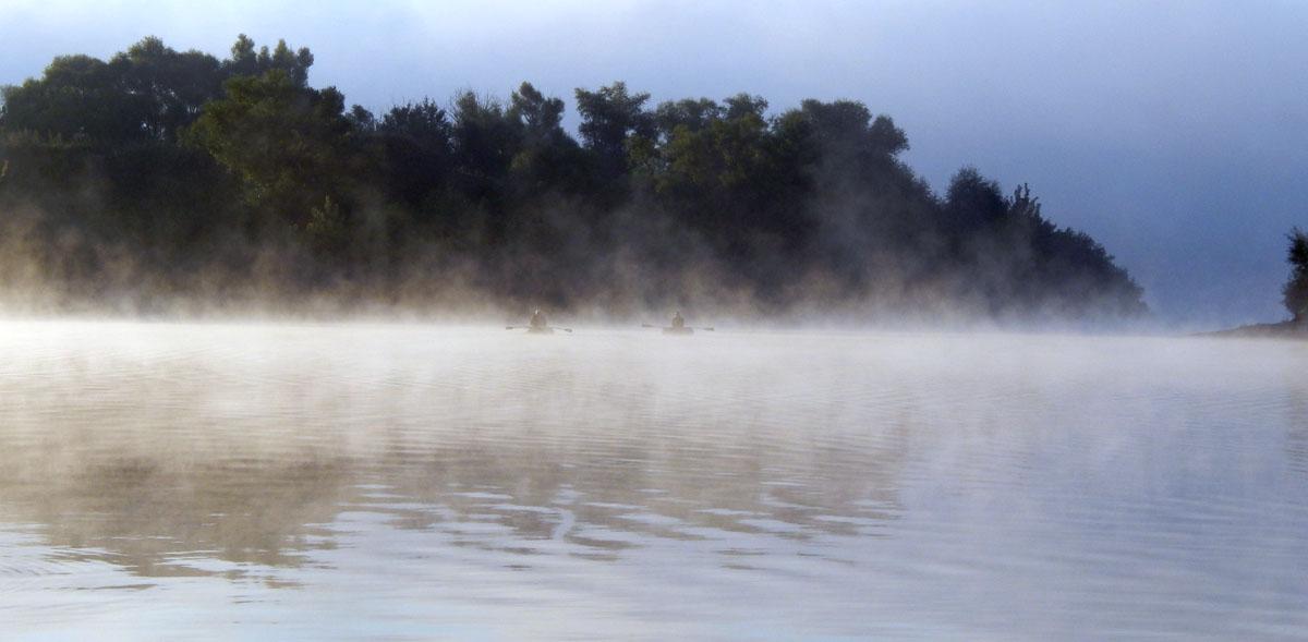 рыбаки в тумане плывут на утиреннюю рыбалку